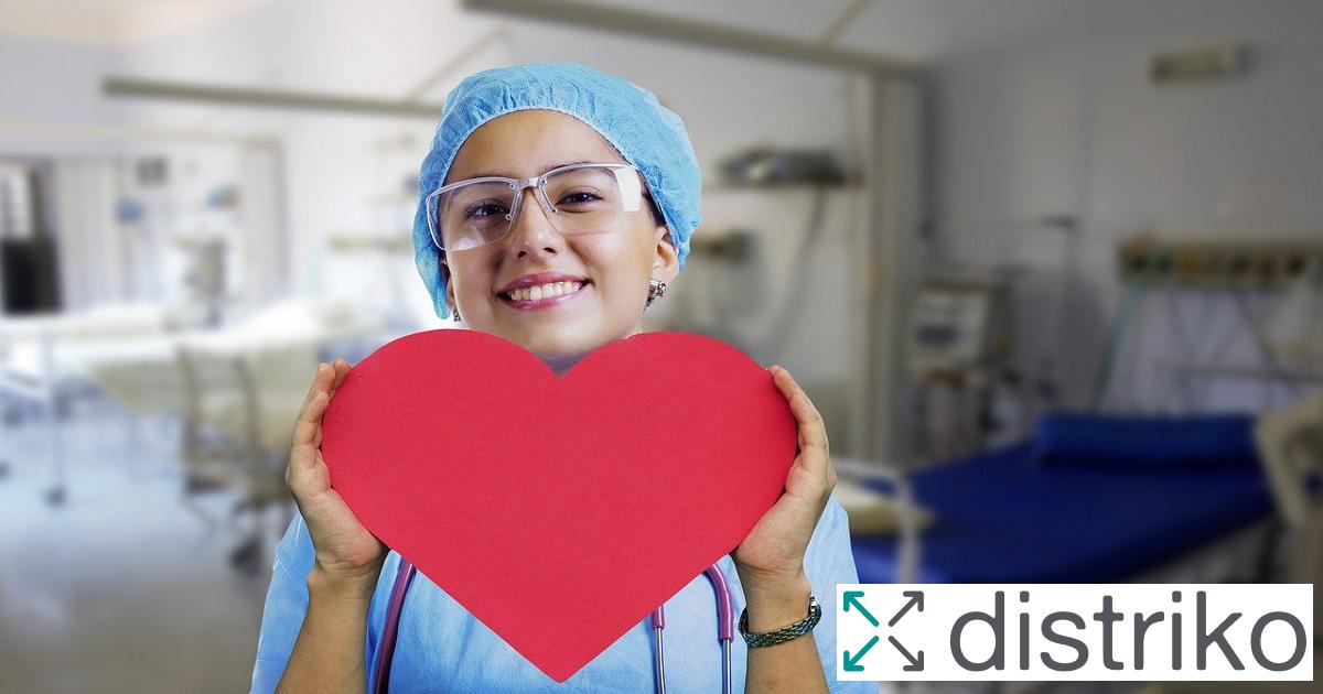 Ein lächelnde Krankenschwester mit Schutzkleidung hält ein rotes Herz in den Händen. Foto für den Artikel Leicht verständliche Sprache im Krankenhaus mit distriko Logo.