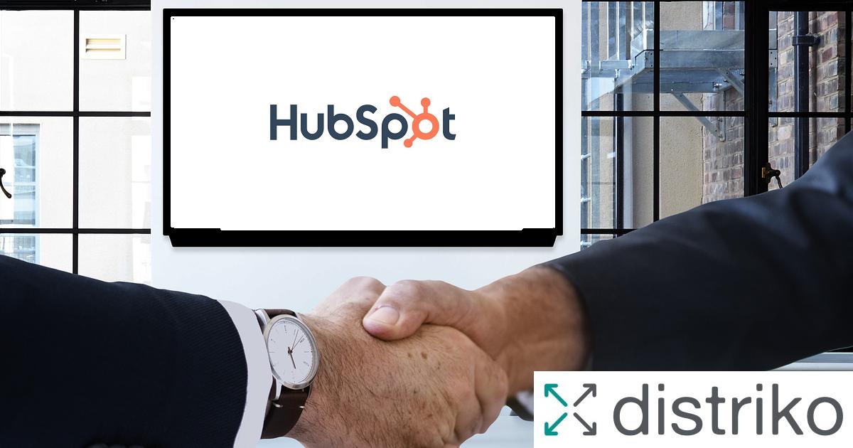 Zwei Geschäftsleute reichen sich die Hände_Der Monitor zeigt das HubSpot Logo und das distriko Logo ist zu sehen.