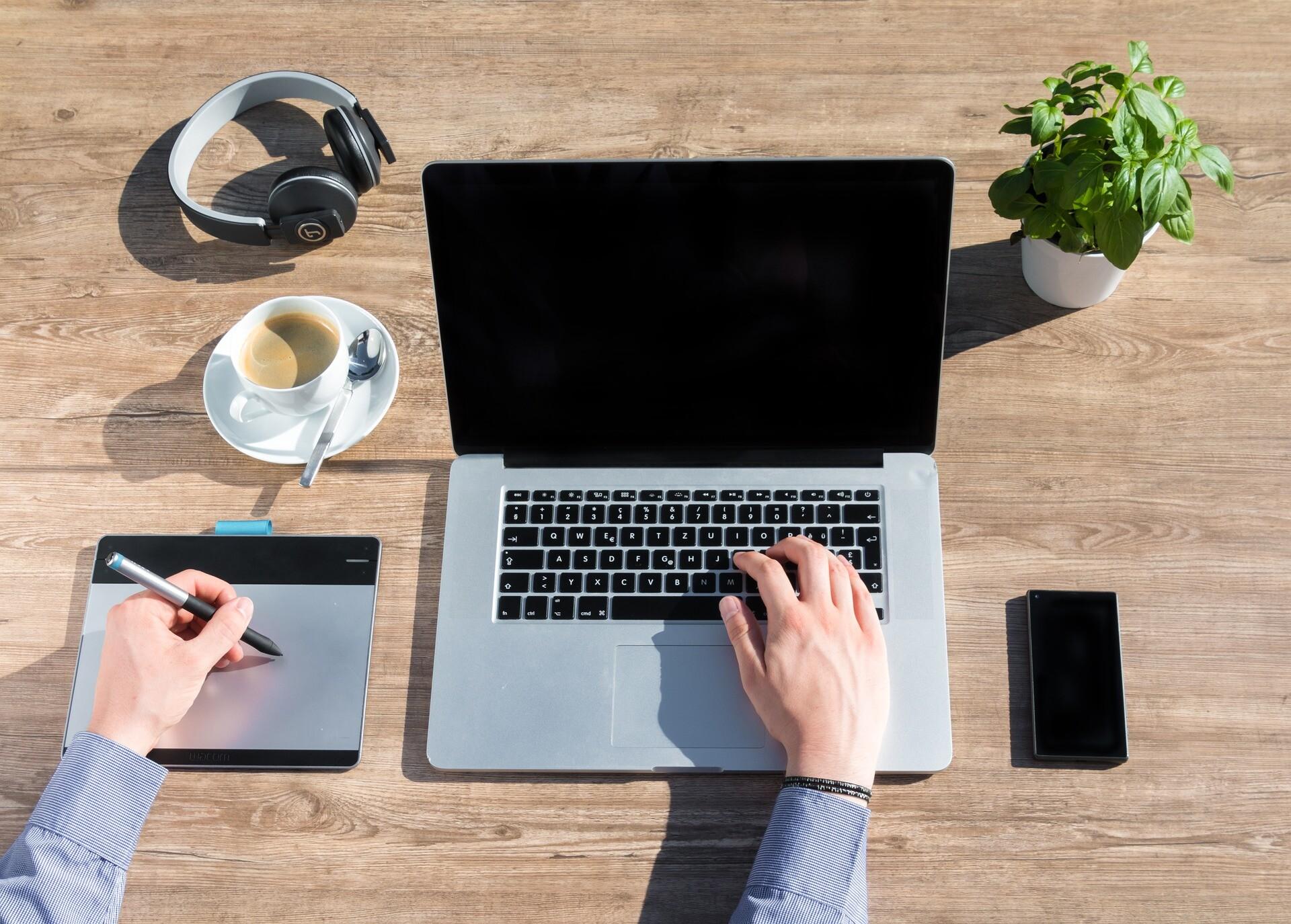 Ein Mediengestalter sitzt an einem Laptop und bedient mit der linken Hand ein digitales Zeichengerät - Barrierefreies Webdesign von distriko