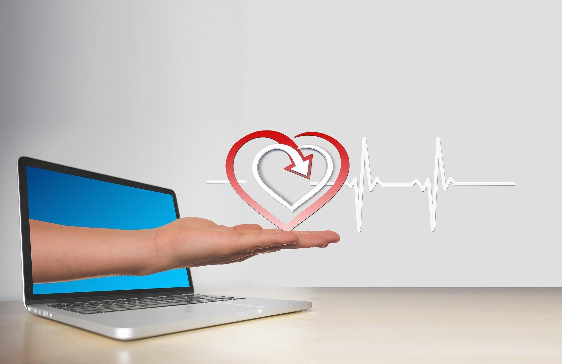 Aus dem Laptop Bildschirm greift eine Hand heraus und hält ein Herz und einen Pulsschlag - Online Beratung von distriko